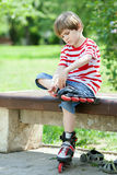 Dzieciak stawiać dalej rolkowe łyżwy obrazy stock