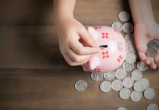 Dzieciak stawia monetę prosiątko bank na rocznika drewna tle obrazy stock