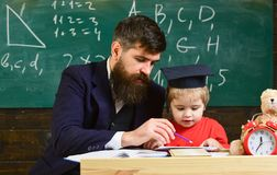 Dzieciak studiuje pojedynczo z nauczycielem, w domu Indywidualny uczy kogoś pojęcie Nauczyciel i uczeń w mortarboard zdjęcia royalty free