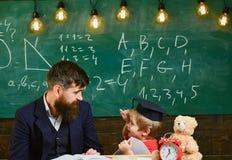 Dzieciak studiuje pojedynczo z nauczycielem, w domu Indywidualny uczy kogoś pojęcie Ojciec z brodą, nauczyciel uczy syna zdjęcia royalty free