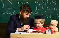 Dzieciak studiuje pojedynczo z nauczycielem, w domu Nauczyciel i uczeń w mortarboard, chalkboard na tle Ojciec z zdjęcie royalty free