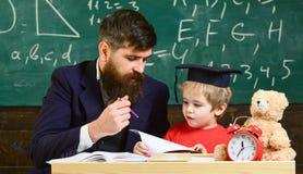 Dzieciak studiuje pojedynczo z nauczycielem, w domu Ojcuje z brodą, nauczyciel uczy syna, chłopiec Nauczyciel wewnątrz i uczeń obrazy royalty free