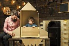 Dzieciak szczęśliwy siedzi w kartonowej ręcznie robiony rakiecie Rodzicielstwa pojęcie Dziecko chłopiec sztuki kosmonauta, astron obraz royalty free