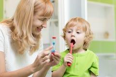 Dzieciak szczotkuje zęby blisko odzwierciedla w łazience Jego macierzysta monitorowanie dokładność i czas cleaning akcja z hourgl zdjęcia royalty free