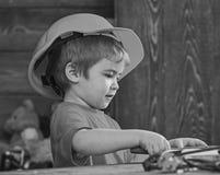 Dzieciak sztuka przy stołem z narzędziami Handcrafting pojęcie Dziecko w hełma śliczny bawić się jako budowniczy lub naprawiacz,  obraz stock