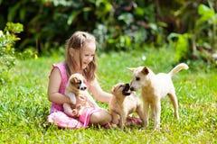 Dzieciak sztuka z szczeniakiem Dzieci i pies w ogródzie obraz royalty free