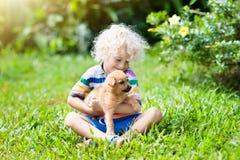 Dzieciak sztuka z szczeniakiem Dzieci i pies w ogródzie fotografia stock