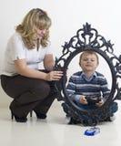 Dzieciak sztuka z zabawkarskim samochodem. Mama chwyt rama Obrazy Stock