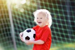 Dzieciak sztuki futbol Dziecko przy boisko do piłki nożnej obraz royalty free