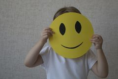 Dzieciak trzyma żółtego okrąg z uśmiech twarzy emoticon zamiast głowy Zdjęcie Royalty Free
