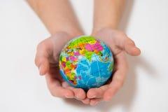 Dzieciak trzyma małą Światową kulę ziemską na ona ręki Obrazy Royalty Free