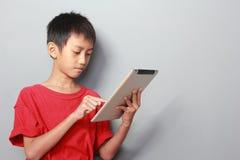 Dzieciak używa pastylkę Fotografia Stock