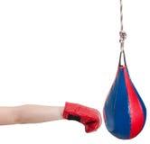 Dzieciak uderza pięścią torbę z bokserskiej rękawiczki ponczami Fotografia Stock