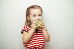 Dzieciak z ślicznym fryzury mieniem i łasowania zielonym jabłkiem obrazy stock