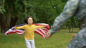 Dzieciak z flaga amerykańskiej przytulenia ojcem w mundurze, rodzinny więź patriotyzm zdjęcie wideo