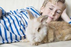 Dzieciak z królikiem w domu Zdjęcia Royalty Free