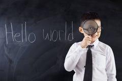 Dzieciak z magnifier i teksta światem Cześć Obraz Stock