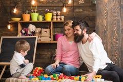 Dzieciak z rodzicami bawić się z plastikowymi blokami, budowy budowa Ojcuje, matka i śliczna syn sztuka z konstruktor cegłami zdjęcie stock