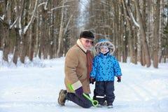 Dzieciak z rodziną zabawę w zima parku zdjęcia royalty free