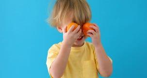 Dzieciak z tangerines mała chłopiec z mandarynkami obrazy stock