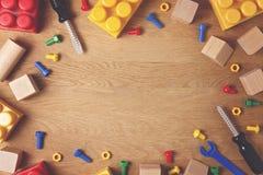 Dzieciak zabawek tło Kolorowi zabawek narzędzia, budowa bloki i sześciany na drewnianym stole, Odgórny widok Mieszkanie nieatutow Zdjęcie Stock