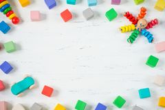 Dzieciak zabawki obramiają drewnianych bloki, ośmiornica, samochód, pyramidion na białym drewnianym tle Odgórny widok Mieszkanie  zdjęcia stock