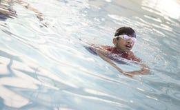 Dzieciaka dopłynięcie z kierowniczym na zewnątrz wody Zdjęcie Stock