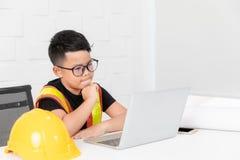 Dzieciaka inżyniera akci spojrzenie jak główkowanie widzieć coś notatnik zdjęcia stock