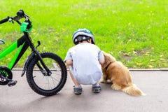 Dzieciaka jeździecki bicykl w miasto parku i zatrzymujący spotykać ślicznego małego psa Dziecko ma zabawę bawić się z zwierzę dom zdjęcie royalty free