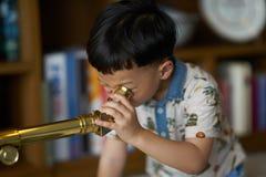 Dzieciaka lub chłopiec koncentratów teleskop indoors fotografia royalty free