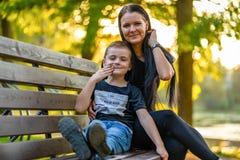 Dzieciaka obsiadanie na Parkowej ławce z Jego mamą w Autum z Kolorowym zdjęcia royalty free