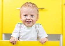 Dzieciaka obsiadanie wśrodku kolor żółty otwierającego kuchni pudełka fotografia stock