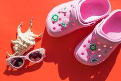 Dzieciaka obuwie Nowożytni Gumowi sandały Różowe trzepnięcie klapy z seashell i okularami przeciwsłonecznymi na czerwonym tle Lat zdjęcia royalty free