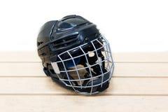 Dzieciaka ` s hokejowy hełm jest na ławce zaciemnia zdjęcia royalty free