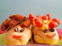 Dzieciaka ` s przyjęcia jedzenie z dwa chlebami patrzeje jak szczęśliwa twarz ludzka Zdjęcie Royalty Free