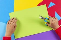Dzieciaka ` s wręcza rozcięcie barwiącego papier z nożycami obrazy royalty free