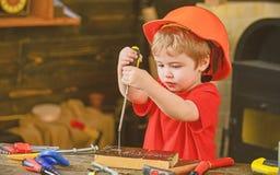 Dzieciaka uczenie używać śrubokręt Skoncentrowany dzieciak w pomarańczowym hełmie pracuje w warsztacie Przyszłościowy zajęcia poj obrazy royalty free