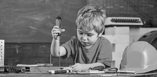 Dzieciaka uczenie używać śrubokręt Skoncentrowany dzieciak pracuje w naprawach warsztatowych Przyszłościowy zajęcia pojęcie zdjęcia stock