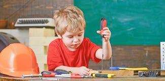 Dzieciaka uczenie używać śrubokręt Skoncentrowany dzieciak pracuje w naprawach warsztatowych Przyszłościowy zajęcia pojęcie obraz royalty free