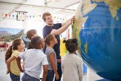 Dzieciaka zegarka prezentacja z gigantyczną kulą ziemską przy nauki centre obrazy stock