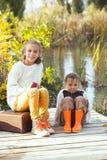 Dzieciaki bawić się blisko jeziora w jesieni Zdjęcia Stock