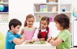 Dzieciaki bawić się grę planszowa w ich pokoju obrazy stock