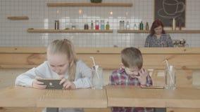 Dzieciaki bawić się gry online na telefonach komórkowych przy kawiarnią zdjęcie wideo