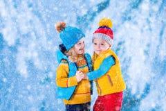 Dzieciaki bawić się outdoors w zimie Fotografia Stock