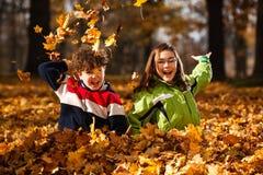 Dzieciaki bawić się w jesień parku Fotografia Royalty Free