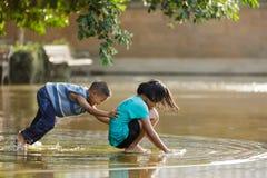 Dzieciaki bawić się w kałuży Obrazy Royalty Free