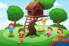 Dzieciaki bawić się wokoło drzewnego domu Fotografia Stock