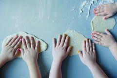 Dzieciaki bawić się z ciastem na błękitnym tle obrazy stock
