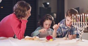 Dzieciaki bawić się z dreidels podczas Hanukka w domu