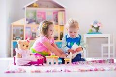 Dzieciaki bawić się z faszerującym lala domem i zwierzętami Zdjęcie Royalty Free